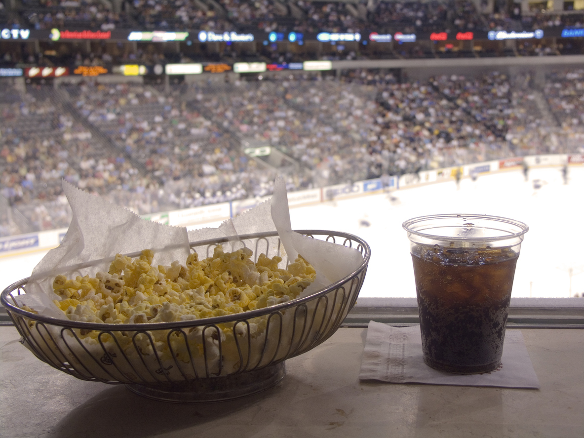 A bowl of popcorn with a glass of soda at a sports game.