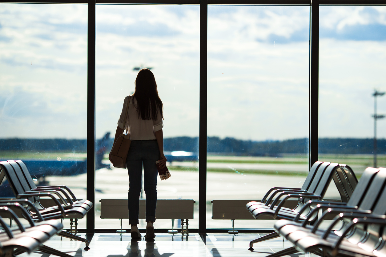 Silhouette of passenger in an airport lounge waiting for flight aircraft