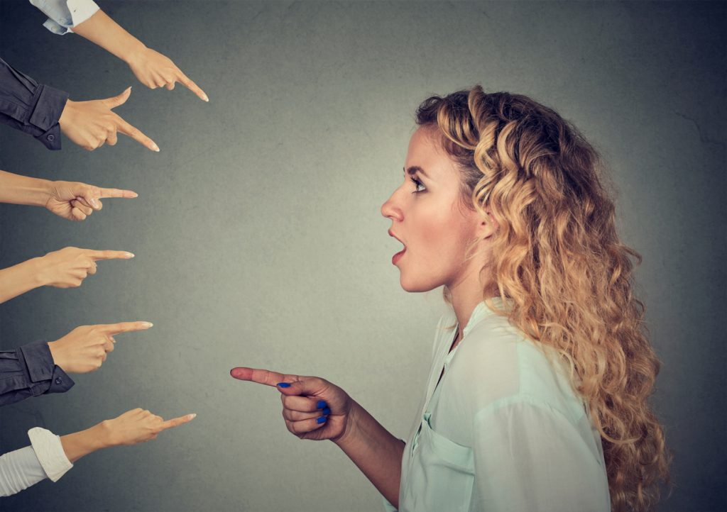 Concept of accusation guilty person woman. Side profile shocked girl pointing against many fingers isolated on grey wall background. Human face expression emotion feeling