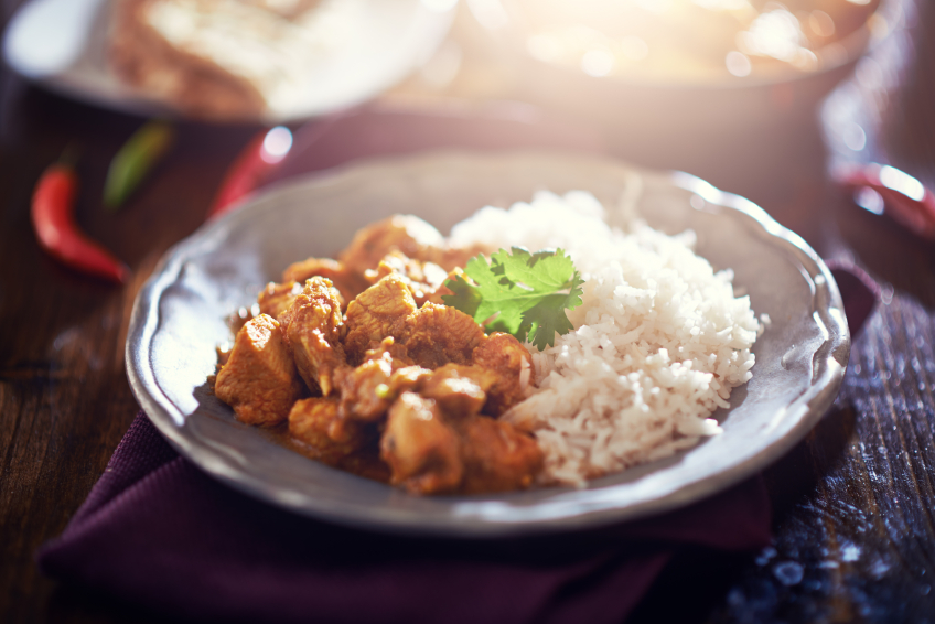 toned image of indian chicken curry with basmati rice