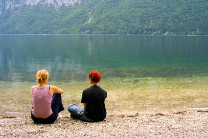 Teens sitting by lake