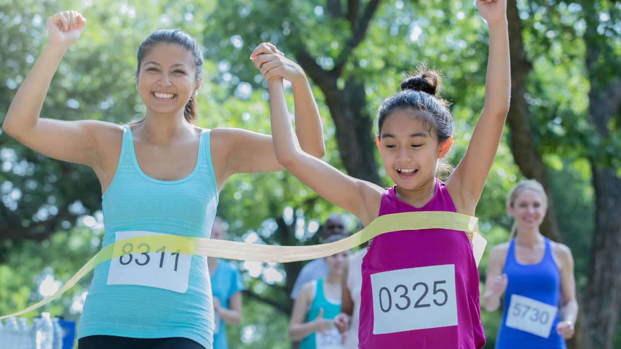 Woman celebrating crossing finish line with her daughter during marathon