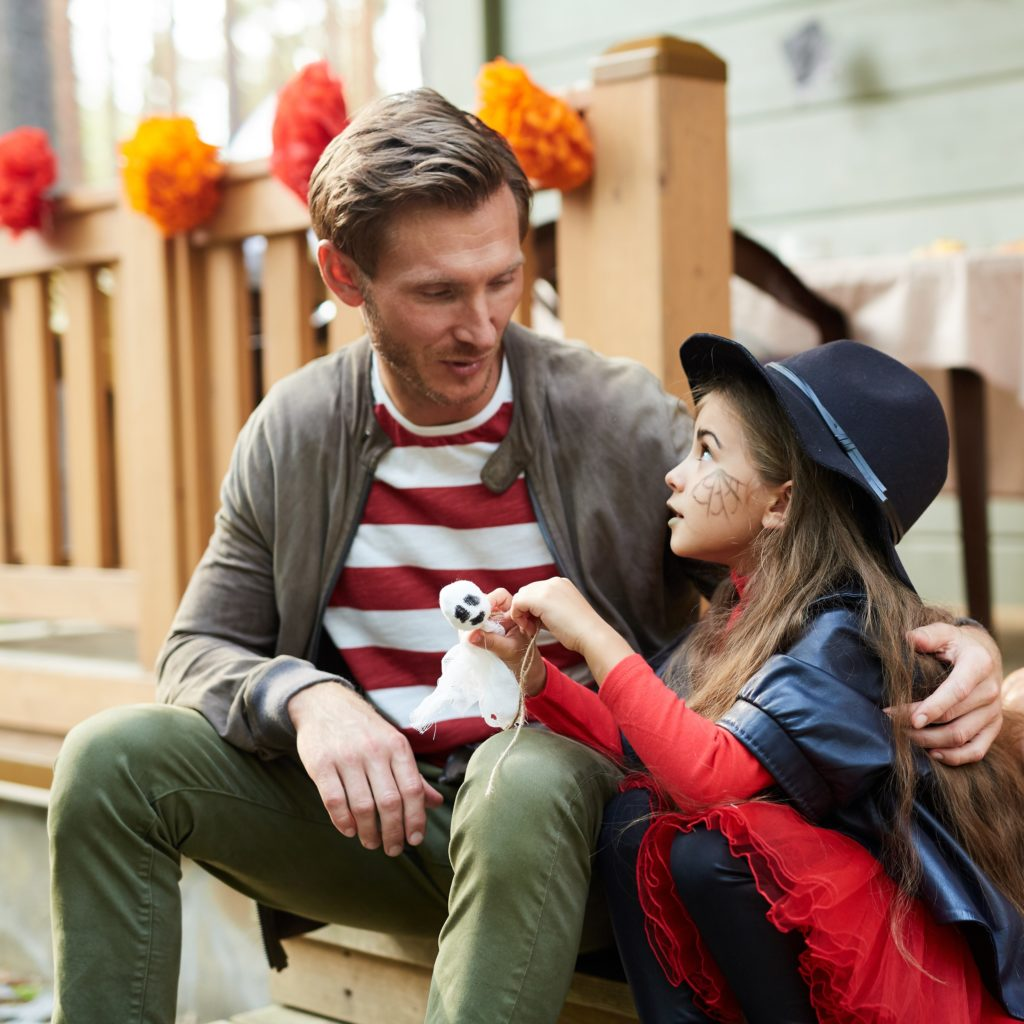 Cute girl in witch costume playing with toy ghost and talking to her dad by terrace of country house