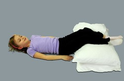 Girl lying on her back with her legs raised on top of pillows.