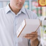 Man doing grocery shopping at the supermarket and reading a food label on a box.