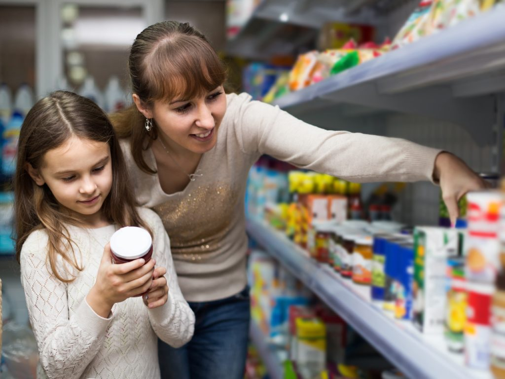 Mom and daughter at the grocery store reading a product ingredient label