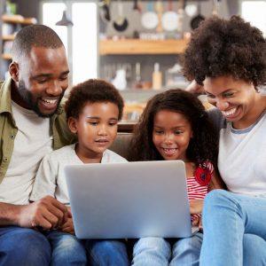 Parents avec leurs 2 enfants qui regardent l'écran de leur ordinateur