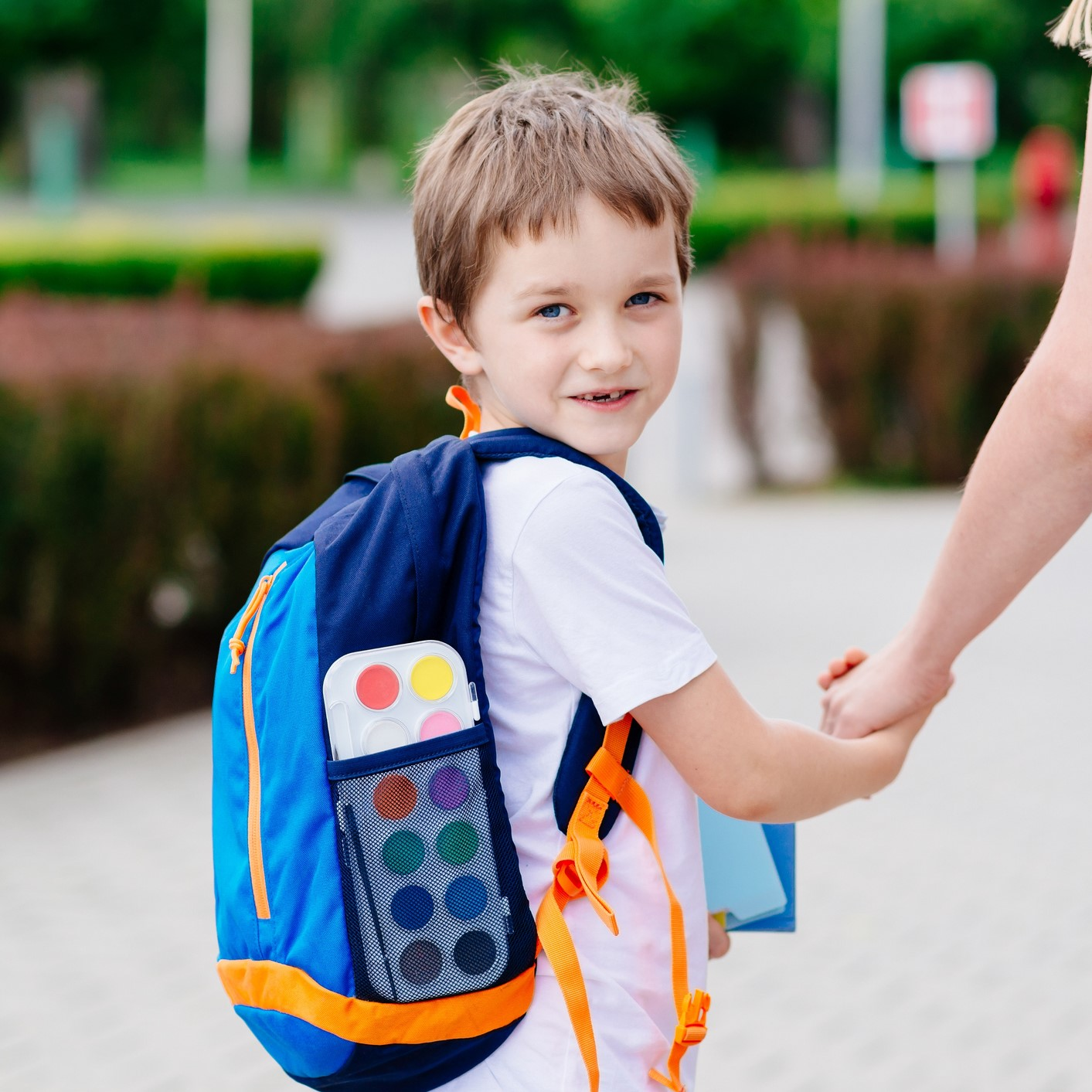 7-year-old boy with a backpack, holding his mother's hand in front of his school