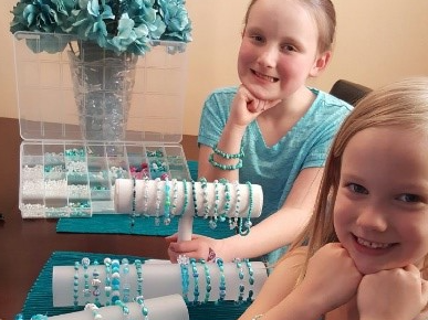 Danica and Delaney pose with their teal bracelets