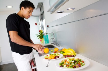Picture of a young adult male making a fruit salad in his kitchen